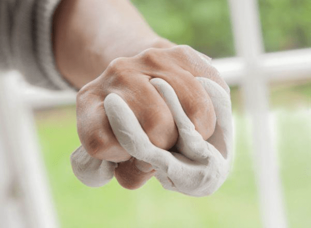 """Image 2: """"Interaction between positive and negative forms (materiel-agency)"""". Photograph demonstrating the clay being pressed through the spaces between the fingers. (Photo: Eva Brænd, 2020). (Heimer, 2020, p. 79)."""